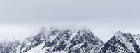Rocky mountains in snow and overcast grey sky at winter