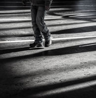Black young man walking alone in urban city with light and dark shadows - Concept of loneliness, outsider or feeling sad and depressed