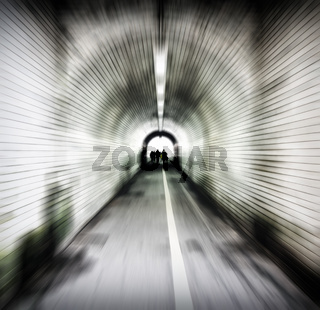 zoom blur image of an old dark pedestrian tunnel with unidentifiable people emerging into the light