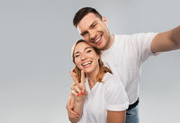 happy couple in white t-shirts taking selfie