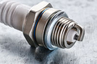 Closeup photo of new spark plug for internal combustion engine on metal background. Space for text