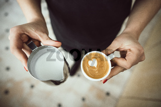 Barista holds two cups, with milk and latte
