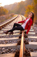 A gorgeous romantic young woman seated down on the railroad tracks, smiling and looking at the camera, in fall scenery outdoors. Fashion concept portrait in beautiful autumn natural light, body shot
