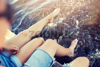 legs of young couple sitting on river berth