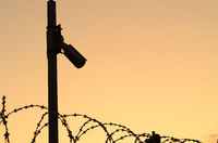 Silhouette of the Security camera on the pole on sunset.Observation of the perimeter of the protected area with barbed wire.Space for text.