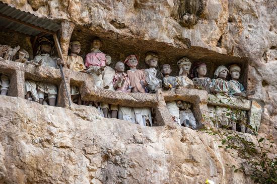 Tau tau, wooden statues representing dead men at burial cave, Tana Toraja, South Sulawesi, Indonesia