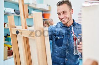 Kreativer Mann beim Malen an Leinwand auf Staffelei