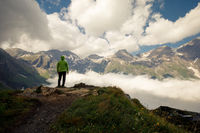 Hiker standing on the Top of a Mountain with Clouds and Fog in the Background. Beauty of nature, tourism and traveling concept