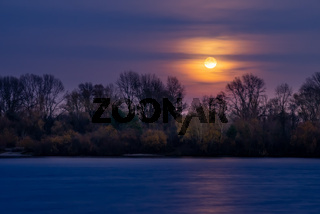 Real full moon over the autumn forest close to Dnieper river in Kiev