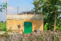Abandoned yellow rocked hut with single green wooden door, tropical green trees and lots of clay