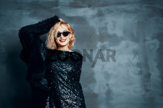 Pretty blonde woman in little black dress posing on grey background with copy space