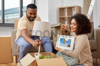 happy couple packing boxes and moving to new home