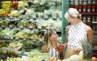 Young mother with her daughter at supermarket