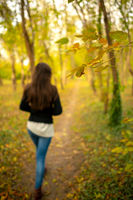 Girl in a park autumn scenery, walking away from the camera, on a footpath through a fall woods landscape. Full length body shot, focus is on a branch with yellow leaves