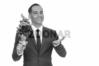 Mature happy Persian businessman holding Happy New Year tree