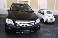 Parkplatz: kleines Auto neben grossem Auto