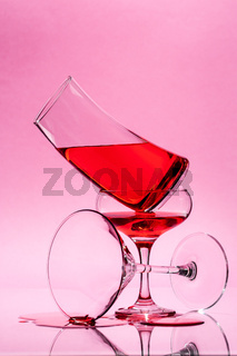 The composition of three glasses of different shapes with a red liquid on a light pink background.