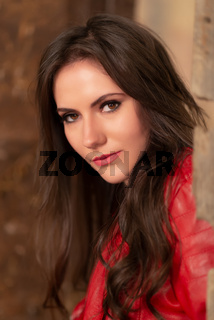 Fashion portrait of a gorgeous young woman in red leather jacket, sitting in a door of an old abandoned building, looking at the camera. Close-up shot, retouched for perfect skin, vibrant colors