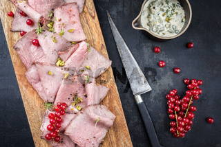 Traditional lunch meat with sliced cold cuts roast beef decorated with remoulade sauce and red ribes as top view on a cutting board