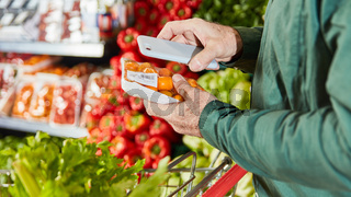 Kunde scannt Packung Lebensmittel mit Smartphone