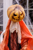 Pumpkin head scarecrow decorating home exterior in Halloween season.