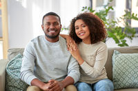 happy african american couple on sofa at home