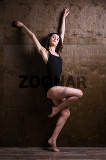Young woman dancer. Young woman modern dancer. Skill ballet dancer posing. dancer posing near the wall. full length portrait of a flexible young woman posing near the wall. Dancer, flexibility
