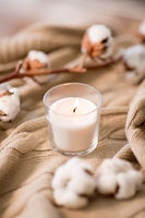 burning candle and cotton flower on blanket