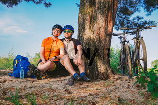 Happy couple with mountain bike sit embracing leisure nature outdoors. happy couple, lead an active lifestyle, stopped in woods near tree take a break. Theme sports and active lifestyle and romance