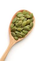 Top view of pumpkin seeds in wooden spoon