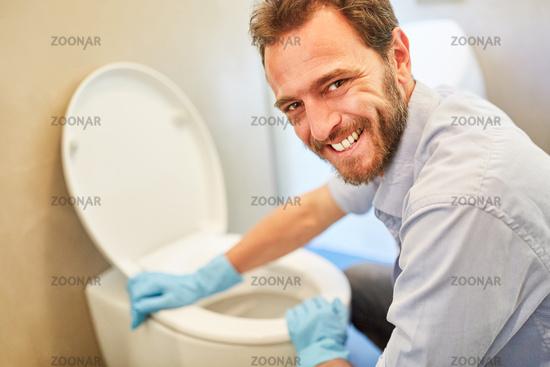 Mann beim WC putzen im Bad