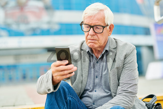 Aged entrepreneur using smartphone on street