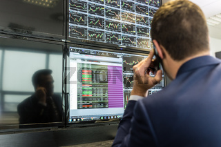 Stock trader looking at market data on computer screens.