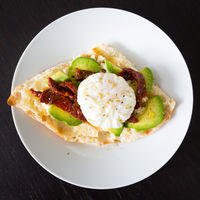 Poached egg on a toasted bun with avocados and dried tomatoes.