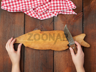 old empty wooden rectangular cutting board and hands hold a sharp knife