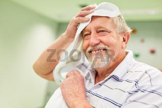 Erschöpfter Senior trocknet sich nach dem Sport die Stirn