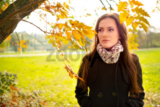 Beautiful romantic girl with perfect skin in autumn park, enjoying the perfect weather in a sunny day. Gorgeous young woman outdoors. Close-up shot in natural light, retouched, vibrant colors