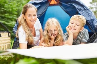Mutter und zwei Kinder vor dem Zelt