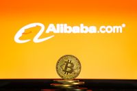 Alibaba logo on a computer screen with a stack of Bitcoin cryptocurency coins.
