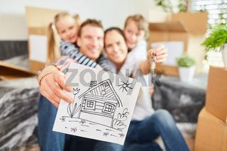 Familie hält Zeichnung vom neuen Eigenheim