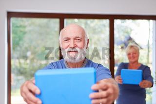 Vitaler Senior macht eine gesunde Rückenübung