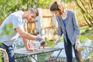 Junges Paar lackiert zusammen einen Tisch