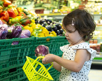 Child shopping eggplants in supermarket. Concept for buying fruits and vegetables in hypermarket