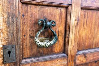 Wooden door with doorknob made of bronze