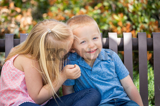 Young Sister and Brother Whispering Secrets On The Bench At The Park