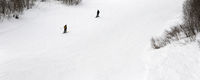 Skier and snowboarder downhill on ski slope at gray winter day