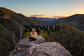 Woman on a rock with views of sunset over mountain valley gorge