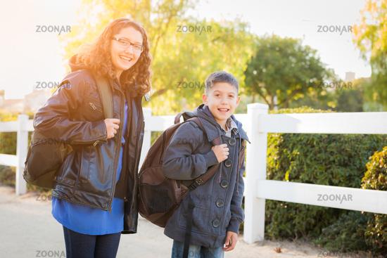 Hispanic Brother and Sister Wearing Backpacks Walking