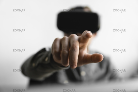Young bearded man with virtual reality glasses trying to touch something or tap some thing in front of what he seeing. Modern technologies. The concept of future technology.