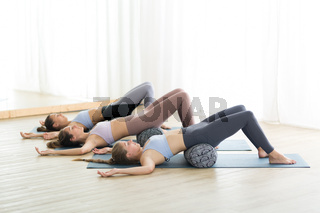 Restorative yoga with a bolster. Group of three young sporty attractive women in yoga studio, lying on bolster cushion, stretching and relaxing during restorative yoga. Healthy active lifestyle